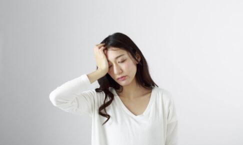 頭に手を当てる女性の片頭痛イメージ